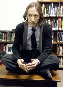 Michael Huemer im Schneidersitz auf einem Schreibtisch